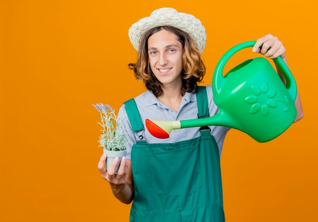 Junger gärtnermann, der overall und hut hält bewässerungsdose trägt