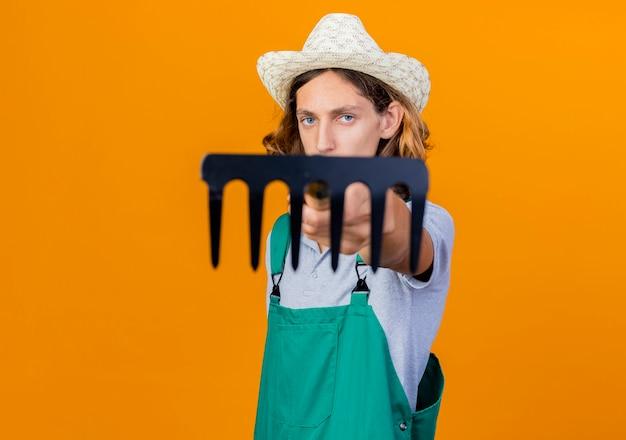 Junger gärtnermann, der overall und hut hält, der mini-rechen hält, der mit ihm auf kamera schaut, die mit ernstem gesicht über orange hintergrund steht