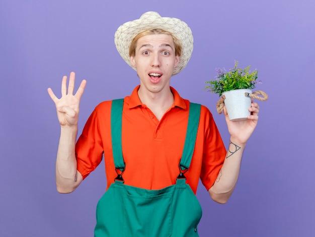 Junger gärtnermann, der overall und hut hält, der topfpflanze lächelnd hält