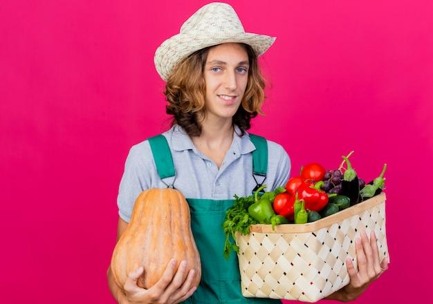 Junger gärtnermann, der overall und hut hält kiste voll frisches gemüse