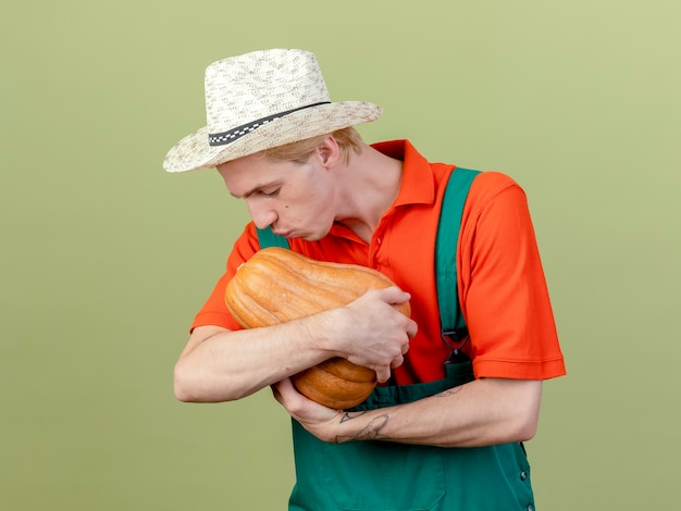 Junger gärtnermann, der overall und hut hält kürbis betrachtet es küssend, das über hellem hintergrund steht