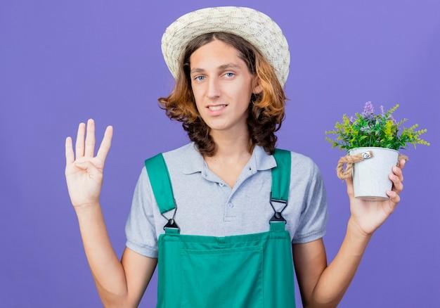 Junger gärtnermann, der overall und hut hält topfpflanze mit lächeln hält