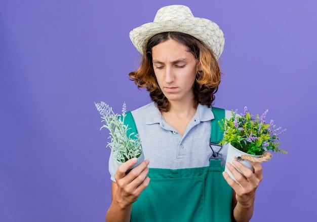 Junger gärtnermann, der overall und hut hält topfpflanzen hält