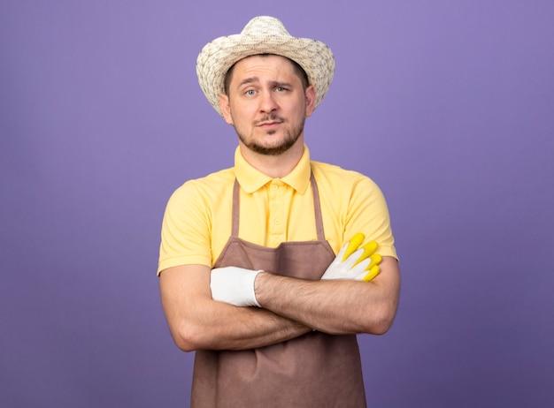Junger gärtnermann, der overall und hut in arbeitshandschuhen mit ernstem gesicht mit verschränkten armen auf brust trägt