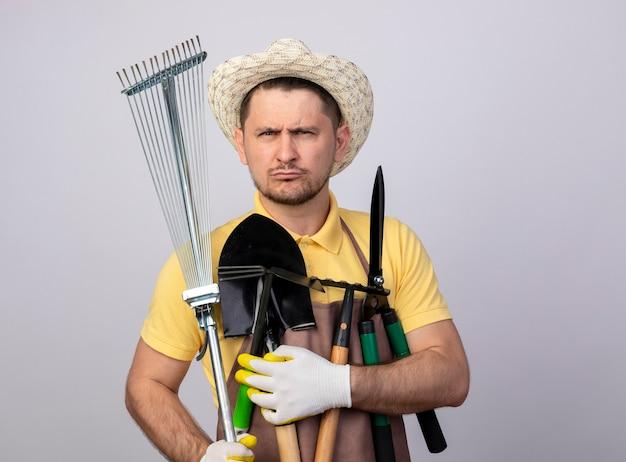 Junger gärtnermann, der overall und hut in arbeitshandschuhen trägt, die gartenausrüstungen mit ernstem stirnrunzeln gesicht halten