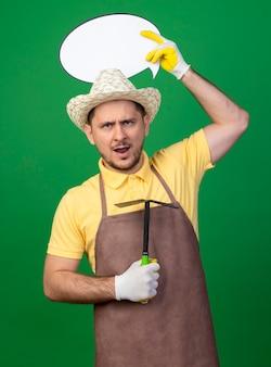 Junger gärtnermann, der overall und hut in arbeitshandschuhen trägt, die mattock und leeres sprechblasenzeichen über seinem kopf mit ernstem wütendem gesicht halten