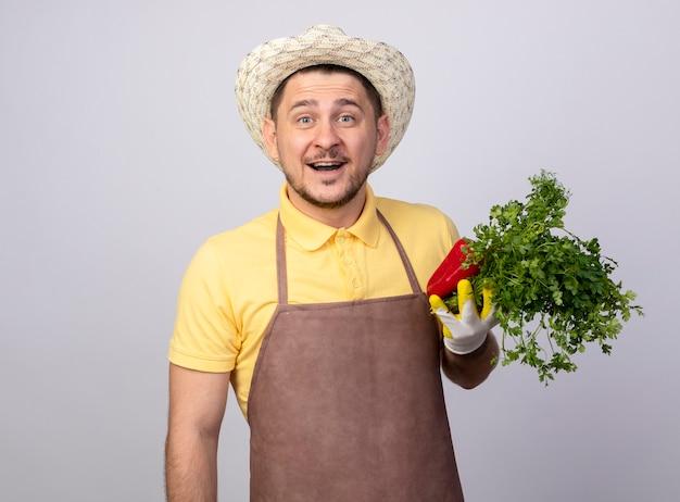 Junger gärtnermann, der overall und hut in arbeitshandschuhen trägt, die rote paprika und frische kräuter lächelnd lächelnd halten