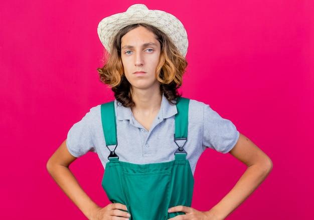 Junger gärtnermann, der overall und hut mit ernstem gesicht mit armen an der hüfte trägt
