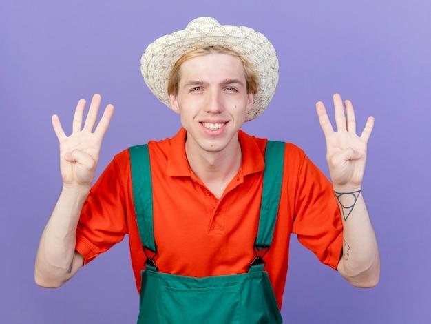 Junger gärtnermann, der overall und hut mit nummer acht trägt