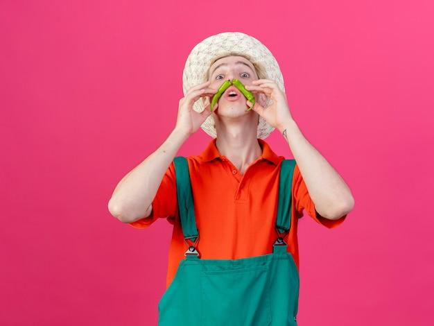 Junger gärtnermann, der overall und hut trägt, der grünen chili-pfeffer hält