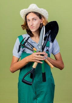 Junger gärtnermann, der overall und hut trägt, die gartenausrüstung halten