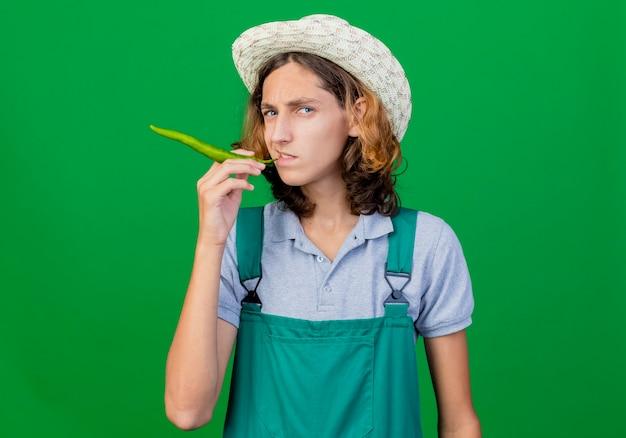 Junger gärtnermann, der overall und hut trägt, die grünen chili-pfeffer wie zigarre halten