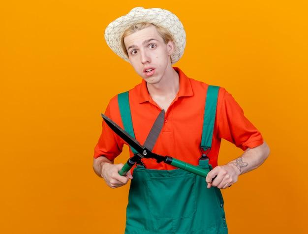 Junger gärtnermann, der overall und hut trägt, die heckenscheren betrachten, die kamera betrachten, die verwirrt über orange hintergrund steht