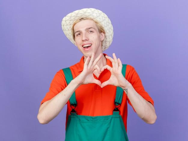 Junger gärtnermann, der overall und hut trägt, die herzgeste mit den fingern machen