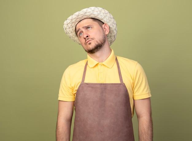 Junger gärtnermann, der overall und hut trägt und beiseite schaut, verwirrt mit traurigem ausdruck auf gesicht, das über lichtwand steht
