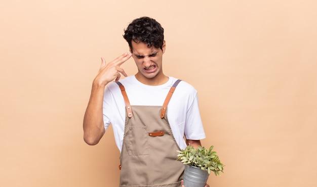 Junger gärtnermann, der unglücklich und gestresst schaut, selbstmordgeste, die waffenzeichen mit hand macht, zeigt auf kopf