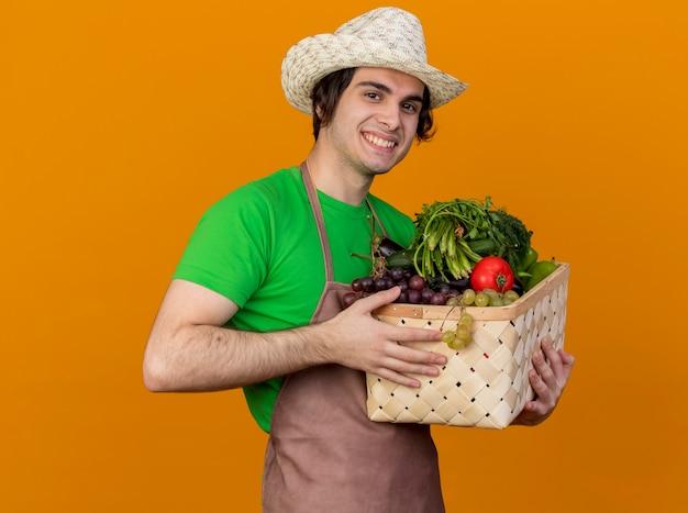 Junger gärtnermann in der schürze und im hut, die kiste voll des gemüses betrachtet kamera betrachtet, die mit glücklichem gesicht über orange hintergrund steht