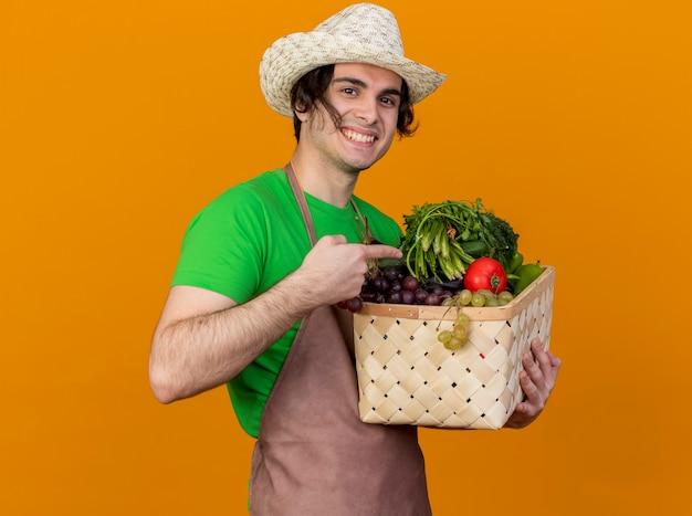 Junger gärtnermann in der schürze und im hut, die kiste voll des gemüses hält, das kamera betrachtet, die fröhlich mit zeigefinger auf kiste zeigt, die über orange hintergrund steht