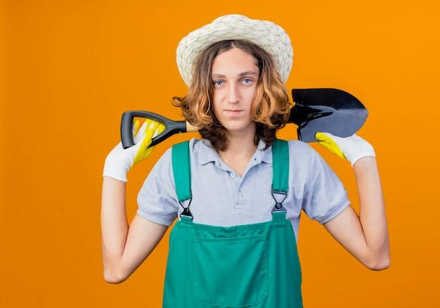 Junger gärtnermann in gummihandschuhen, die overall und hut halten schaufel mit lächeln tragen