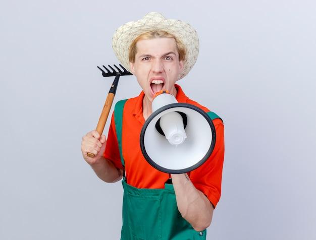 Junger gärtnermann mit overall und hut, der einen mini-rechen schwingt und mit wütendem ausdruck zum megaphon schreit