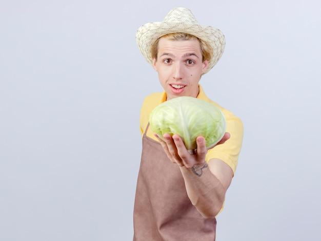 Junger gärtnermann mit overall und hut, der kohl mit einem lächeln auf einem glücklichen gesicht zeigt