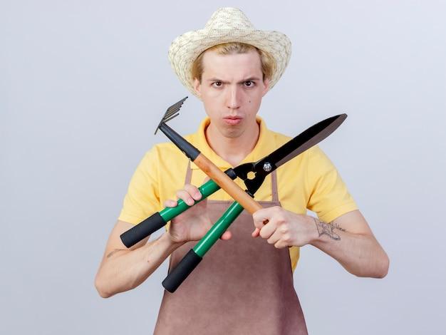 Junger gärtnermann mit overall und hut, der mini-rechen und heckenschere hält, die hände mit ernstem gesicht kreuzen
