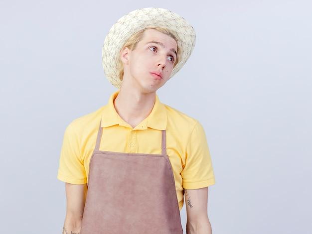 Junger gärtnermann mit overall und hut, der verwirrt beiseite schaut