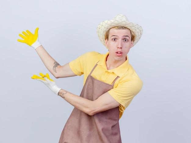 Junger gärtnermann mit overall und hut in gummihandschuhen, der etwas mit verwirrten händen präsentiert