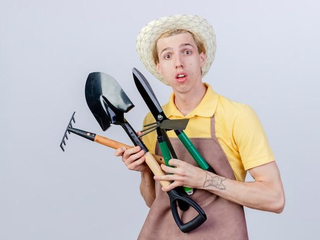 Junger gärtnermann mit overall und hut mit hackenrechen und heckenscheren überrascht