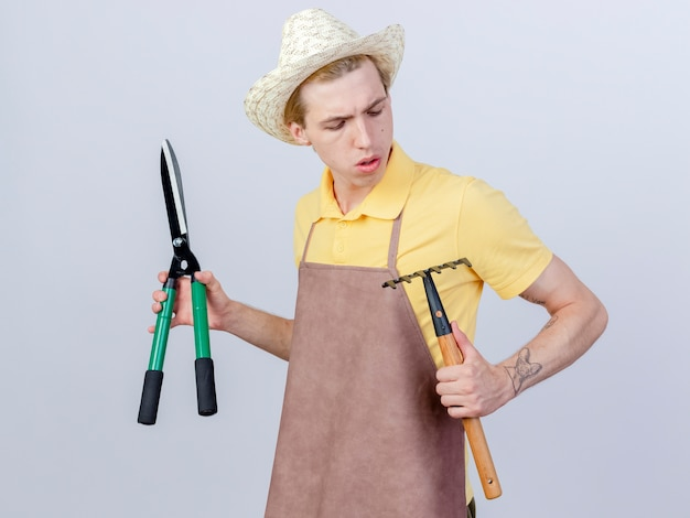 Junger gärtnermann mit overall und hut mit mini-rechen und heckenscheren, der mit ernstem gesicht nach unten schaut