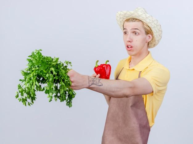 Junger gärtnermann mit overall und hut mit roter paprika, der frische kräuter zeigt, die überrascht beiseite schauen