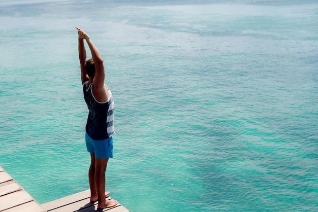 Junger gebräunter athlet, der stretchübungen auf einem ozeandock macht.