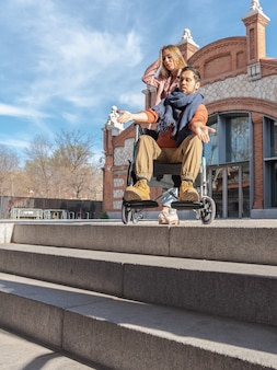 Junger gelähmter mann mit mädchen in einem rollstuhl frustriert vor einigen treppen