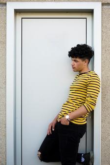 Junger gelockter hispanischer mann, der auf türgehäuse sich lehnt