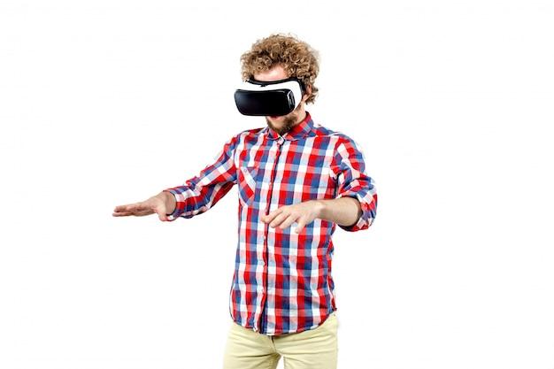 Junger gelockter mann im karierten hemd unter verwendung eines vr-kopfhörers und eines exp