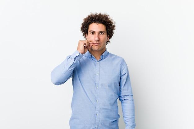 Junger gelockter reifer mann, der ein elegantes hemd mit den fingern auf den lippen hält ein geheimnis trägt.