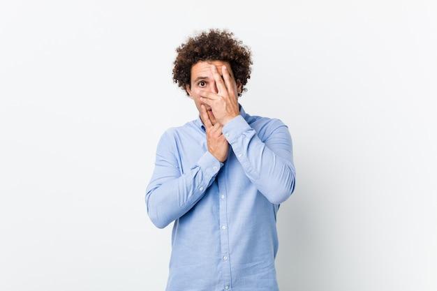 Junger gelockter reifer mann, der ein elegantes hemdblinzeln durch die finger erschrocken und nervös trägt.