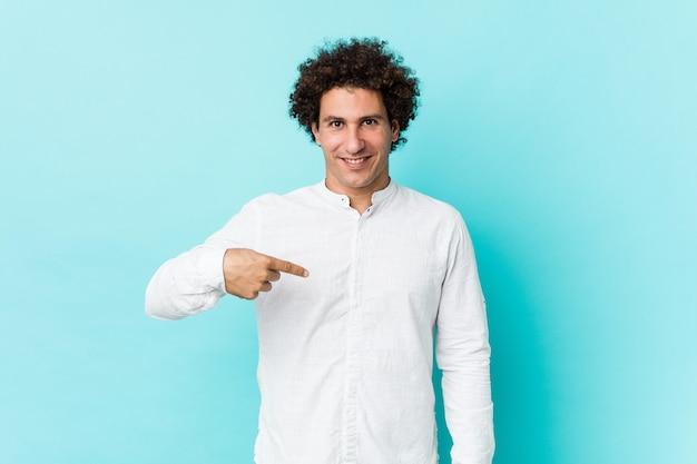 Junger gelockter reifer mann, der eine elegante hemdperson eigenhändig zeigt auf einen hemdkopienraum, stolz und überzeugt trägt