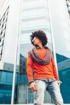 Junger gelockter schwarzafrikaner mit gläsern geht durch die stadt