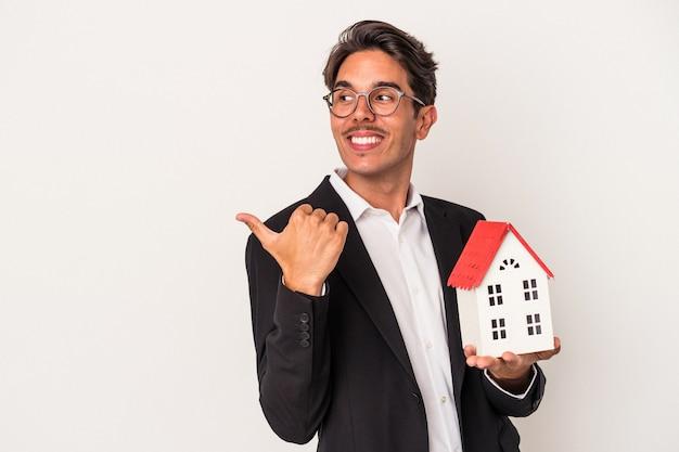 Junger gemischter geschäftsmann, der ein spielzeughaus hält, das auf weißem hintergrund lokalisiert wird, zeigt mit dem daumenfinger weg, lacht und sorglos.