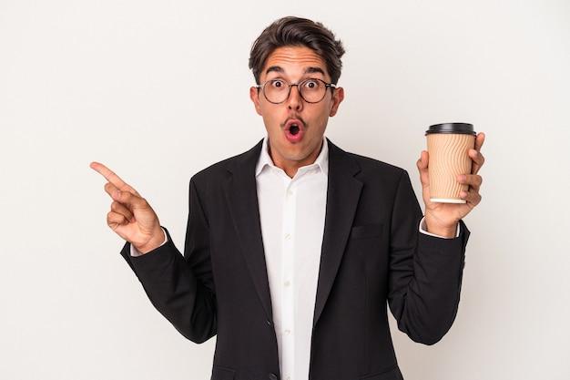 Junger gemischter geschäftsmann, der kaffee zum mitnehmen hält, isoliert auf weißem hintergrund, der auf die seite zeigt?