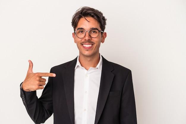 Junger gemischter geschäftsmann isoliert auf weißem hintergrund, der mit der hand auf einen hemdkopierraum zeigt, stolz und selbstbewusst