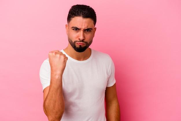 Junger gemischter rassenmann lokalisiert auf rosa hintergrund, der faust zur kamera, aggressiven gesichtsausdruck zeigt.