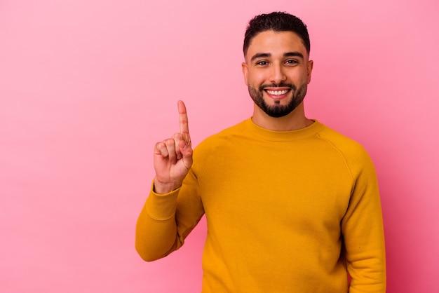 Junger gemischter rassenmann lokalisiert auf rosa hintergrund, der nummer eins mit finger zeigt.