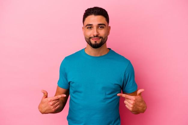 Junger gemischter rassenmann lokalisiert auf rosa hintergrundperson, die von hand auf einen hemdkopierraum zeigt, stolz und zuversichtlich