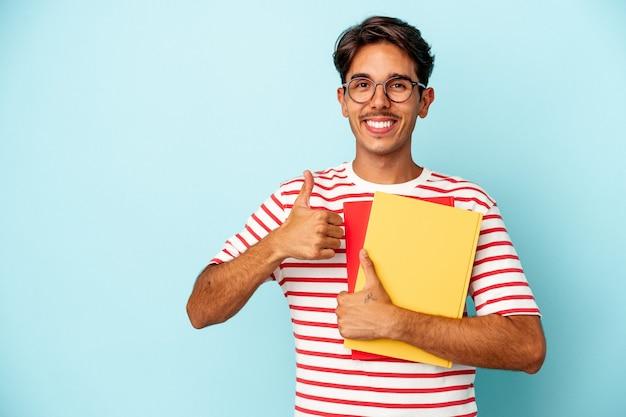 Junger gemischter studentenmann, der bücher auf blauem hintergrund isoliert hält, lächelt und hebt den daumen nach oben