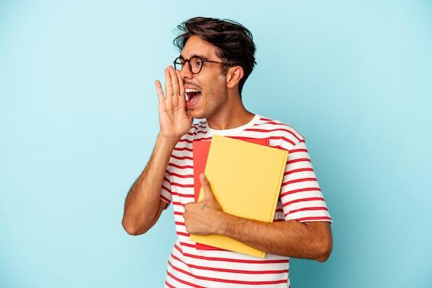 Junger gemischter studentenmann, der bücher auf blauem hintergrund isoliert hält, schreit und die handfläche in der nähe des geöffneten mundes hält.