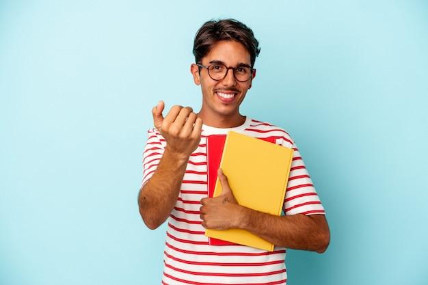Junger gemischter studentenmann, der bücher einzeln auf blauem hintergrund hält und mit dem finger auf sie zeigt, als ob er einladen würde, näher zu kommen.