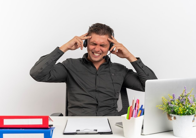 Junger genervter blonder büroangestelltermann auf kopfhörern sitzt am schreibtisch mit bürowerkzeugen unter verwendung des laptops hält kopf mit geschlossenen augen lokalisiert auf weißem hintergrund mit kopienraum