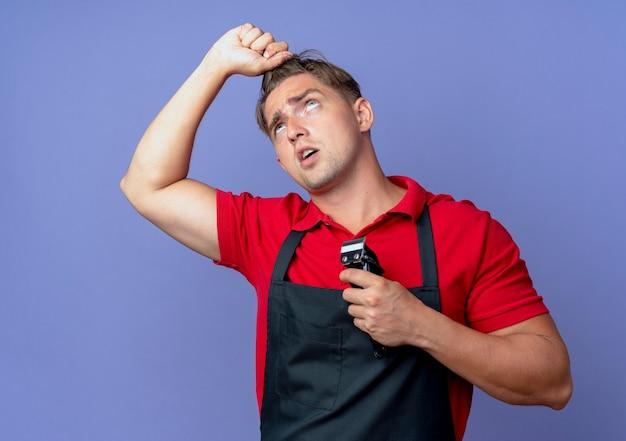 Junger genervter blonder männlicher friseur in uniform hält haare, die nach oben schauen und haarschneidemaschine isoliert auf violettem raum mit kopierraum halten